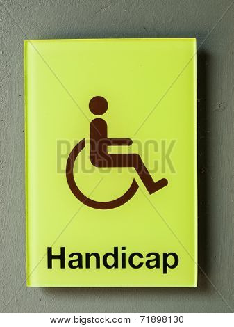 Green Glass Handicap Sign On Grey Wall