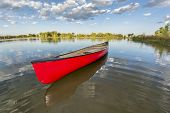 stock photo of collins  - red canoe on a calm lake in a fisheye perspective - JPG