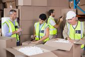 picture of vest  - Warehouse workers in yellow vests preparing a shipment in a large warehouse - JPG