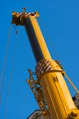 picture of hydraulics  - Big and yellow construction hydraulic crane for heavy lifting on blue sky - JPG