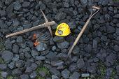 stock photo of power-shovel  - Shovel pickaxe gloves mining helmet in the background heap of coal  - JPG