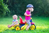 stock photo of tricycle  - Two happy kids adorable curly toddler girl and a funny cute baby boy brother and sister playing together riding a bike first colorful tricycle having fun in the garden on a sunny summer day - JPG