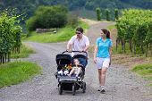 image of twin baby girls  - Young active parents hiking in the mountains with a double twin stroller with two children brother and sister baby boy and toddler girl - JPG
