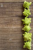stock photo of romanesco  - Romanesco cauliflower on a wooden table background - JPG