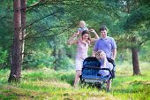 image of twin baby girls  - Active family young parents and their two little children adorable toddler girl and a cute funny baby boy hiking together in a pine forest pushing an all terrain twin stroller - JPG