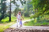 image of little young child children girl toddler  - Happy active woman playing with a cute little child acdorable toddler girl in a blue dress having fun together enjoying hiking in a beautiful sunny pine wood forest on a warm summer day - JPG