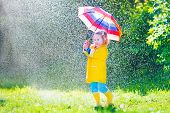 pic of coat  - Funny cute curly toddler girl wearing yellow waterproof coat and boots holding colorful umbrella playing in the garden by rain and sun weather on a warm autumn or sumemr day - JPG