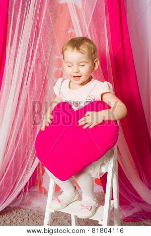 Little girl with a heart toy in tutu skirt