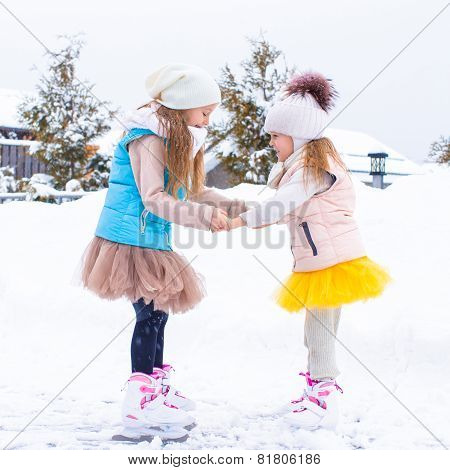 Adorable little girls skating on ice rink in winter snow day