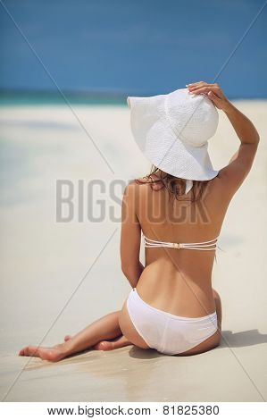 Beautiful woman in a white bikini and hat on a tropical beach.