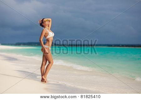 Woman sunbathing standing, looking up