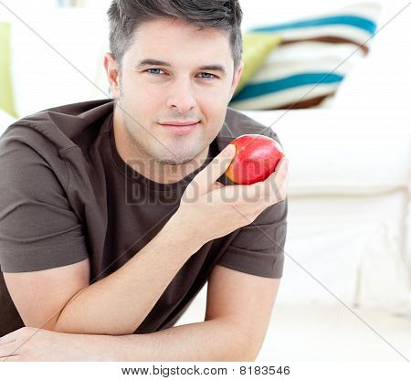Jolly Man Holding A Red Apple Lying On The Floor