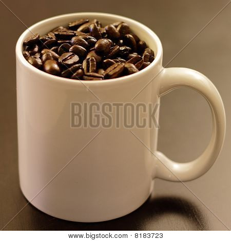 Mug full of coffee beans