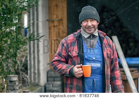 Man In A Warm Jacket And Beanie Drinking Coffee