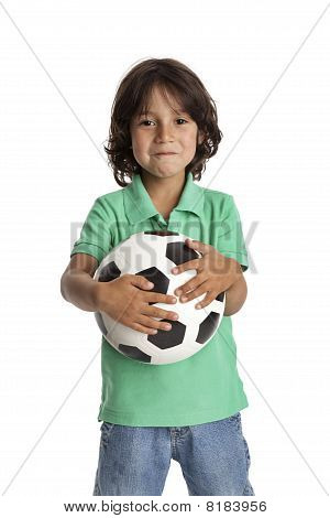 Proud little boy holding a soccer ball
