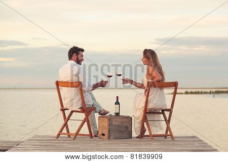 Couple Drinking Red Wine At The Seaside On A Jetty