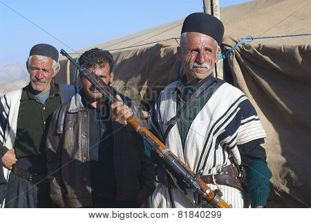 Man in traditional dress holds a rifle, circa Isfahan, Iran.