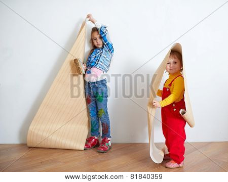 girls hanging wallpaper. Decorating the wall