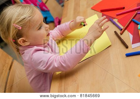 Blond Cute Girl Is Painting A Picture