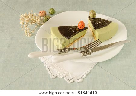 Two pieces of easter cake with tea match decorated chocolate ganache and sweet-stuff eggs on white p