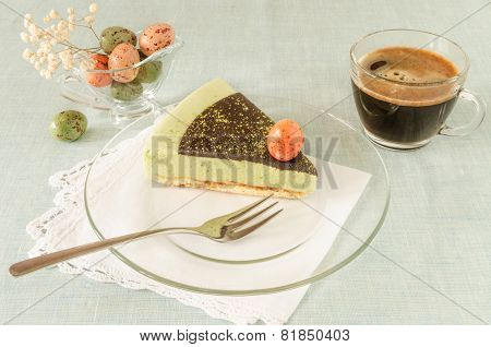 Piece of easter cake with tea match decorated chocolate ganache and sweet-stuff eggs on glass plate
