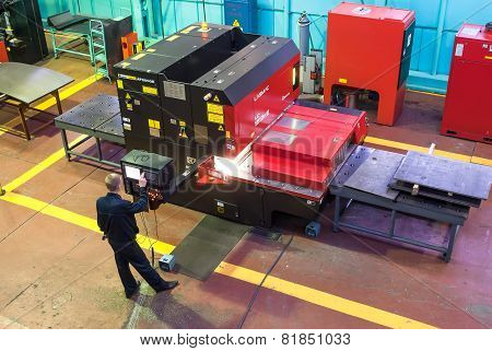 Worker operates computerized metalworking machine