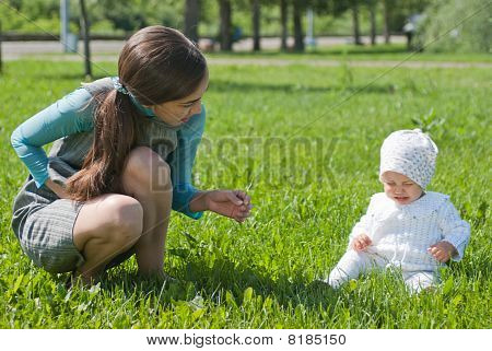 Mother Comforting Her Daughter Crying On The Lawn In The Park