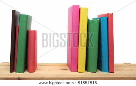 Books on wooden shelf close-up isolated white background. No labels, blank spine.
