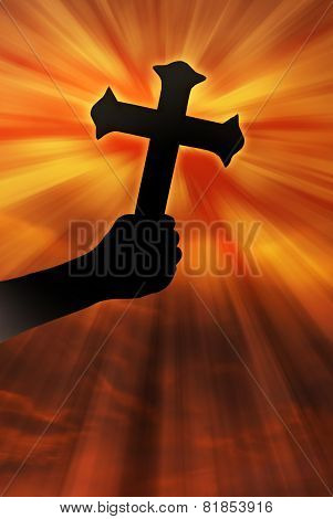 Silhouette Of Cross Held Up At Sunset