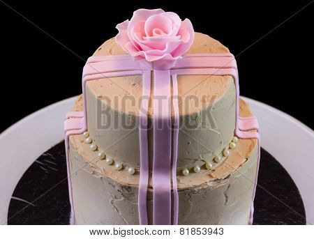 One beige cake with a pink rose