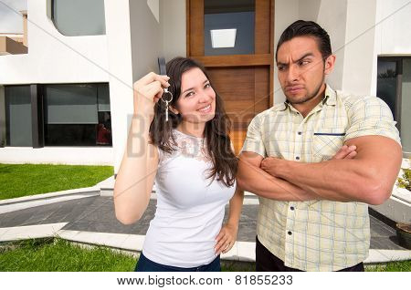 suspicious husband looking at wife holding key to their house