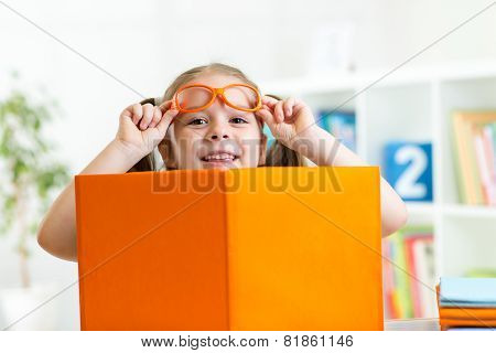 clever child girl behind of open book indoor