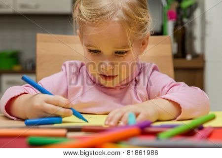 Cute Blond Girl With A Lots Of Crayons