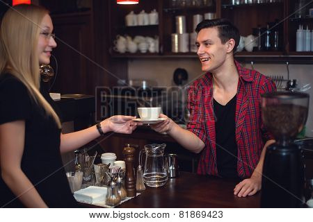 Hipster barista pass order cup of coffee or tea with smile to beautiful blond girl