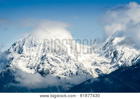Moutain pass in the Alps with snow and clouds