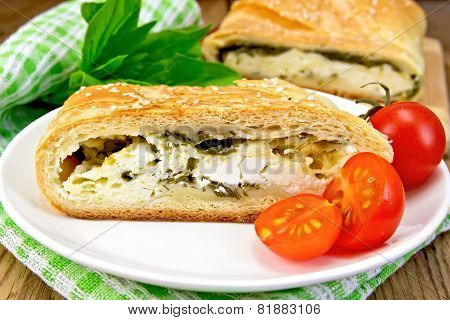 Roll filled with spinach and cheese on wooden board
