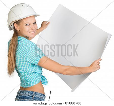 Woman in hard hat showing blank sheet of drawing paper