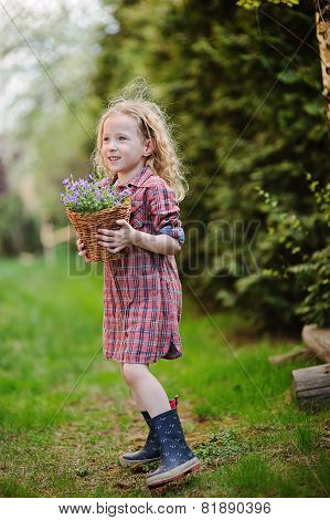 child girl with bluebell flowers in spring garden
