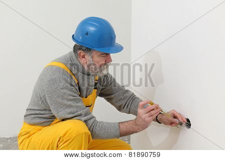 Electrician At Construction Site Testing Installation