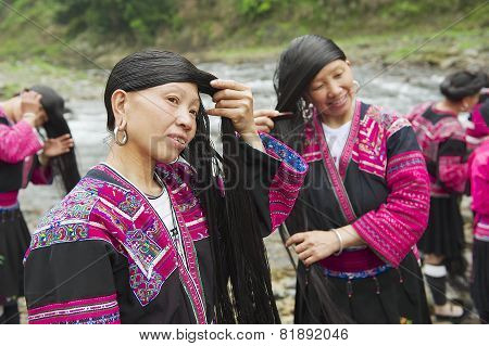 Women brush and style long hair in Longji village, China.