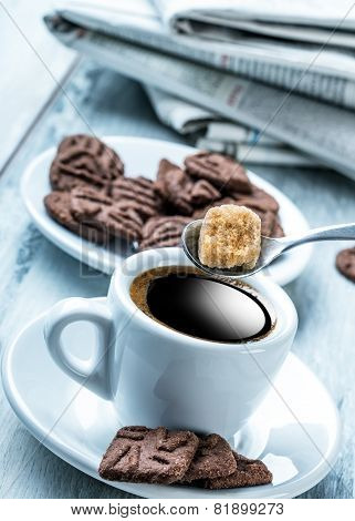 Cup of coffee spoon with cane sugar, chocolate biscuits and the background newspaper.