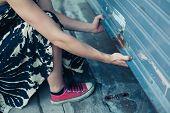 image of roller door  - A woman is unlocking and opening a garage door - JPG