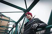 foto of anarchists  - Punk guy with beanie posing in the city streets - JPG