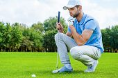 stock photo of ball cap  - Cropped image of young golfer kneeling near the golf ball and holding hand on chin - JPG