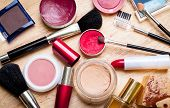 picture of girly  - colorful makeup items scattered across a wooden surface - JPG