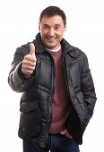 picture of down jacket  - Handsome man in a down jacket showing his thumb up - JPG