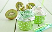 stock photo of frozen  - Frozen vanilla yogurt with fresh kiwi in polka dot paper cup - JPG