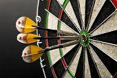 foto of bullseye  - Three darts in bullseye of dartboard on black backgraund - JPG