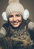 pic of muffs  - Beautiful woman with hat and ear muffs and cat smiling at camera - JPG