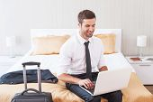 stock photo of tied  - Handsome young man in shirt and tie working on laptop and smiling while sitting on the bed in hotel room - JPG